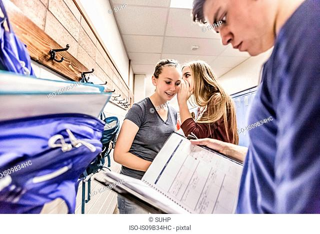 Irritated teenage boy reading notebook whilst girls whispering in high school locker room