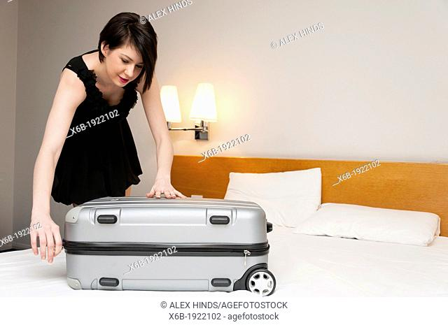 Woman packing suitcase in hotel room