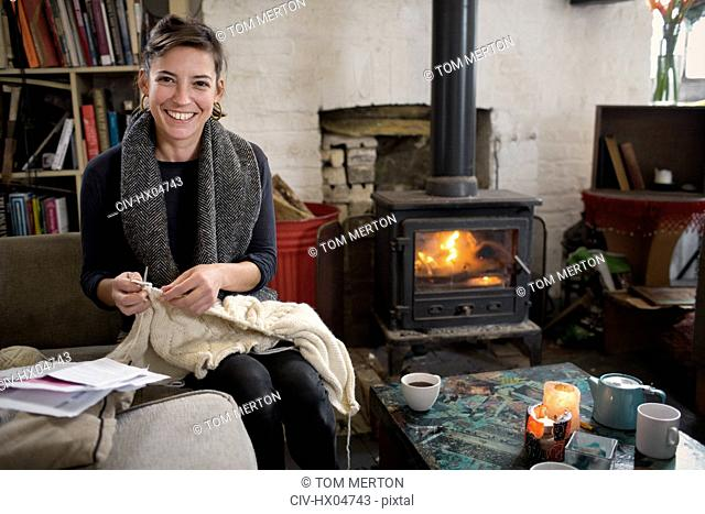 Portrait smiling, confident woman knitting by fireplace in living room