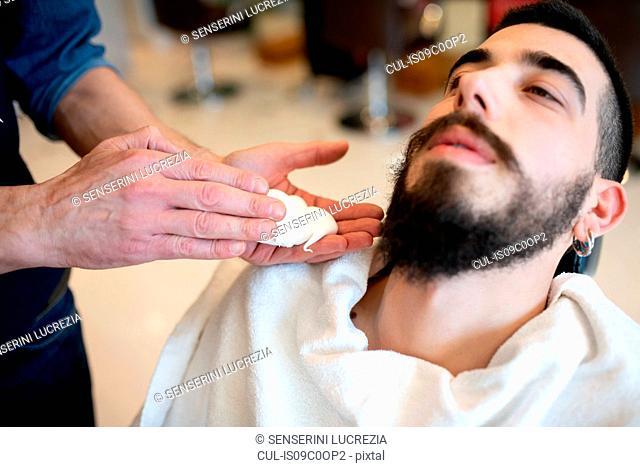Hairdresser preparing to shave customer's beard in barber shop