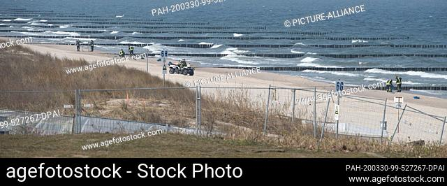 28 March 2020, Mecklenburg-Western Pomerania, Koserow: Firefighters of the municipality of Koserow collect black, greasy lumps with shovels on the beach between...