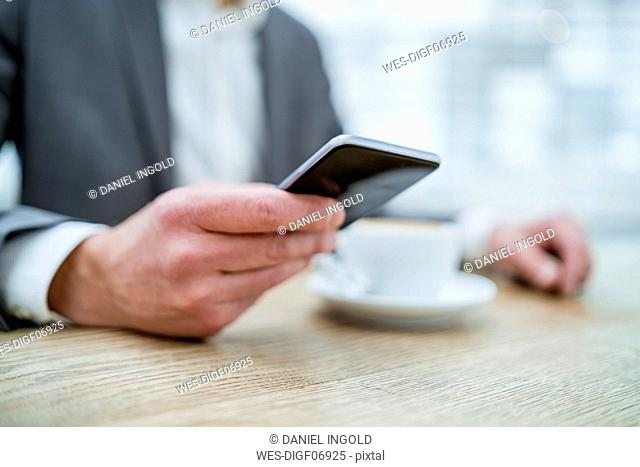 Close-up of businessman using cell phone in a cafe