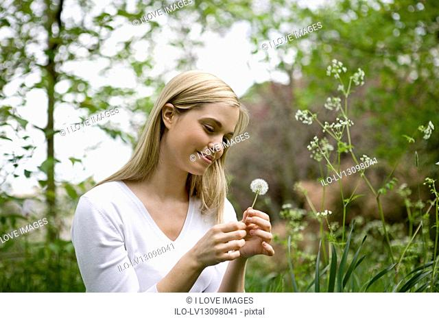 A young woman looking at a dandelion clock