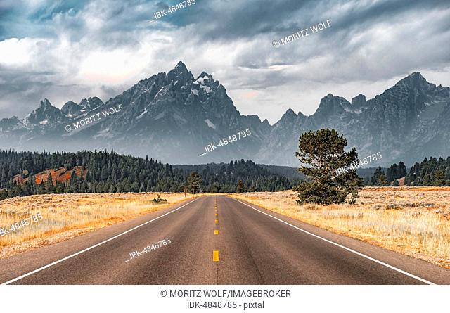 Highway in front of rugged mountains with cloudy skies, Grand Teton Range, Grand Teton National Park, Wyoming, USA