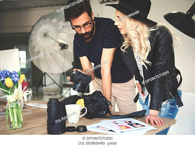 Photographer and stylist reviewing photographs on photography studio camera
