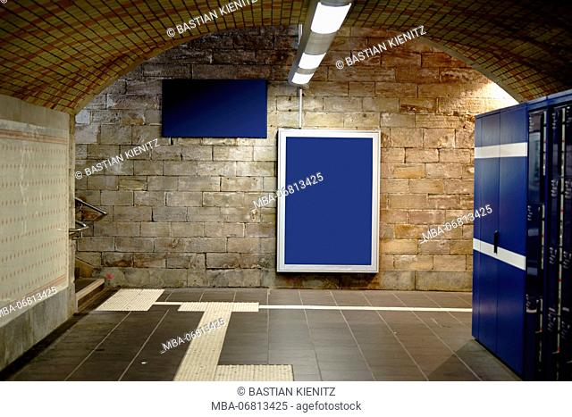 An illuminateded and tiled railway station tunnel with ceiling lamps and frames for advertising poster