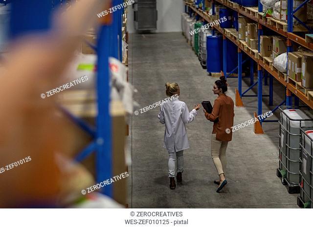Two women walking in warehouse