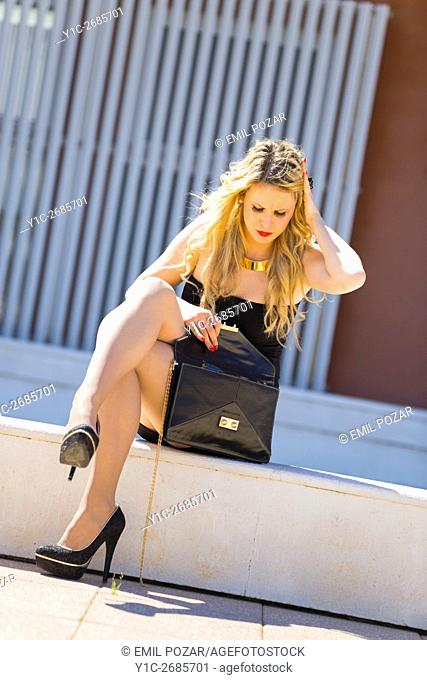 Blonde young woman sitting searching something into her purse