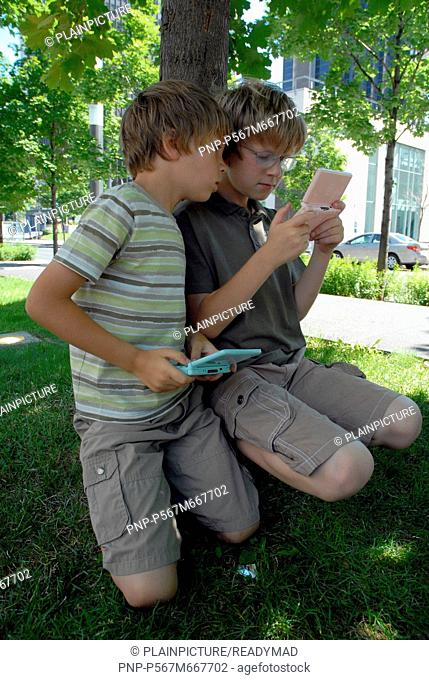 Two boys are playing Nintendo DS
