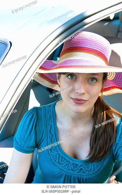 Woman in colorful hat sitting in car