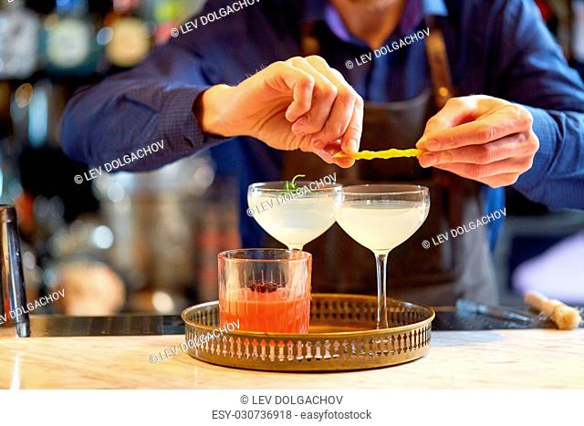 alcohol drinks, people and luxury concept - bartender with glasses and lemon peel preparing cocktail at bar