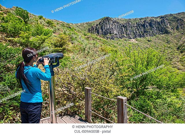 Hiker looking through binoculars at Hallasan the highest mountain in Korea, Jeju Island, South Korea