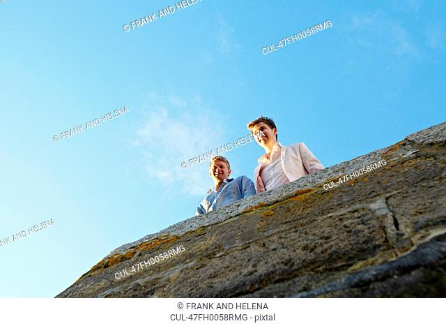 Men looking over edge of stone wall