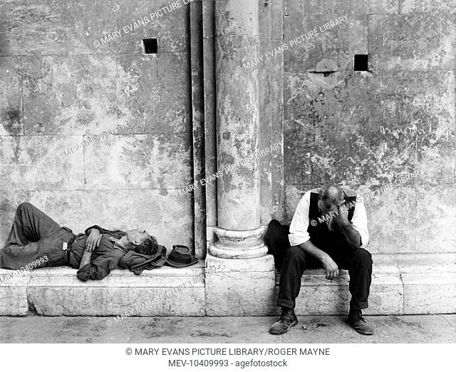 Two middle aged men while away the time in Modena, northern Italy. One of them is asleep, while the other sits with his head resting on his fist