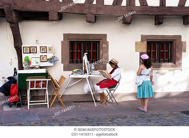 Little girl watching street artist painting by half-timbered house, 'La Petite France' district, Strasbourg, Alsace, France