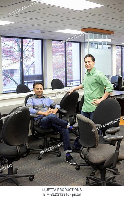 Businessmen smiling in conference room