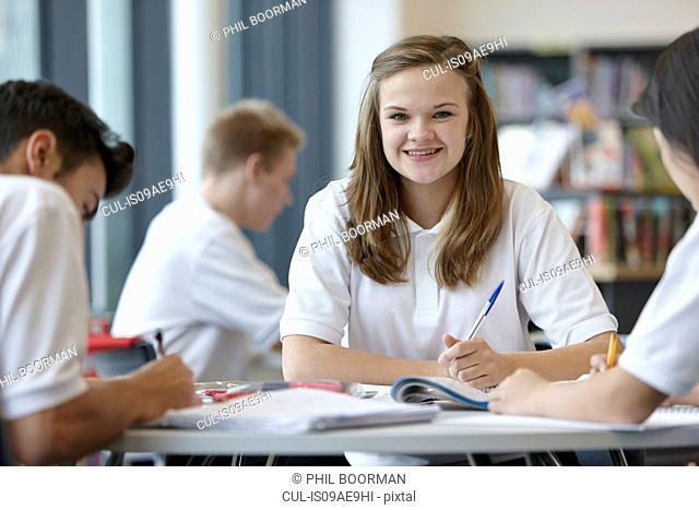 Group of teenagers working in school classroom