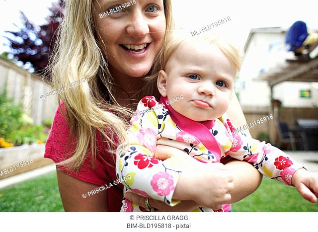Caucasian mother holding daughter in backyard