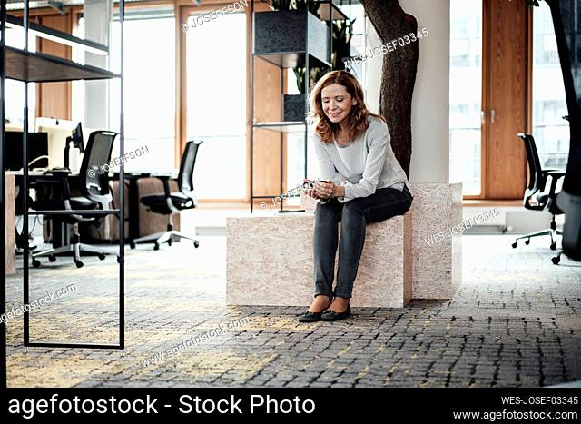 Female entrepreneur using smart phone while sitting on retaining wall at office