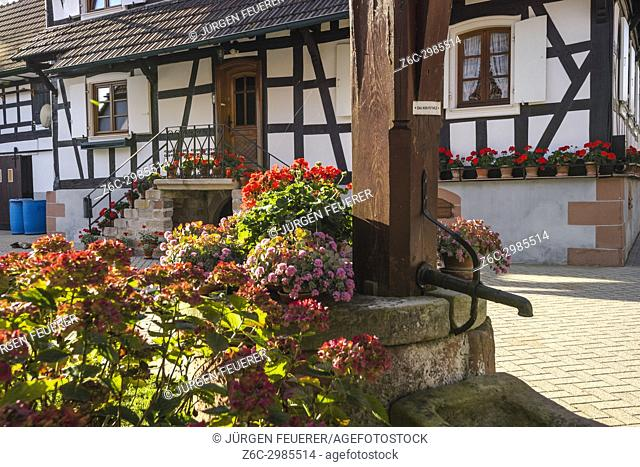 half-timbered houses with flower decoration and old well of Hunspach in the autumn, small village in Northern Alsace, North Vosges, France
