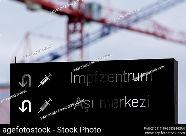 17 March 2021, North Rhine-Westphalia, Cologne: Cranes can be seen on a construction site behind a signboard in German and Turkish script