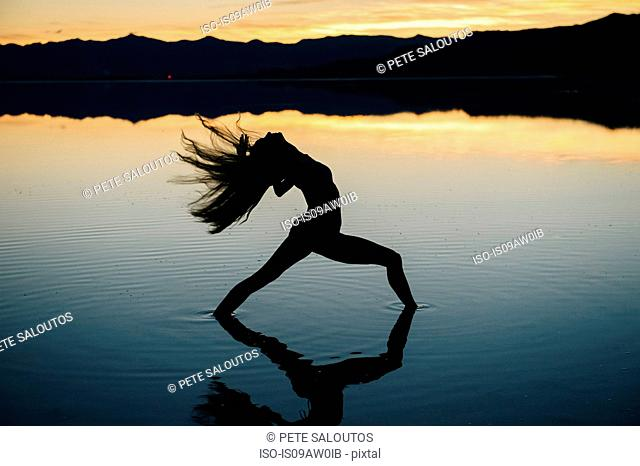 Silhouetted female dancer throwing back her long hair in lake at sunset, Bonneville Salt Flats, Utah, USA