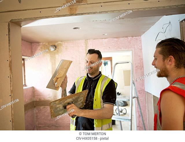 Construction workers plastering in house