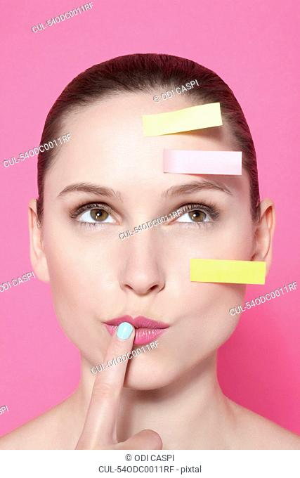 Woman with sticky notes on face