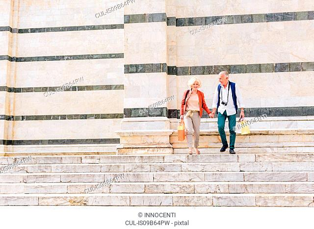 Tourist couple moving down Siena cathedral stairway, Tuscany, Italy