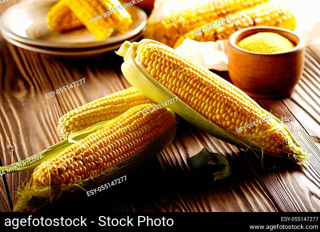 Kitchen table with raw and grilled sweet corn cob on baking paper and grits in wooden bowl