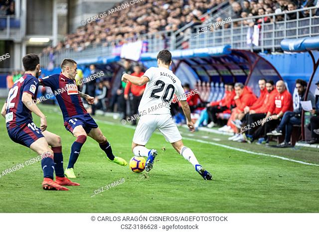 Marco Asensio (R), Ruben Peña (C) and Paulo Oliveira (L) dispute the ball during the La Liga match between Eibar and Real Madrid CF at Ipurua Stadium on...