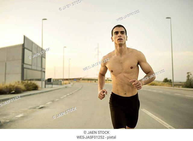 Young shirtless man running on road