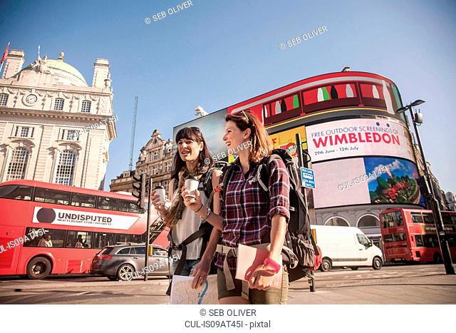 Two women backpackers with takeaway coffee, Piccadilly Circus, London, UK