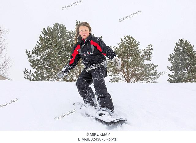 Serious girl riding snowboard on hill in winter