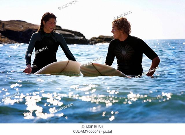 Couple sitting on surfboards in the water smiling