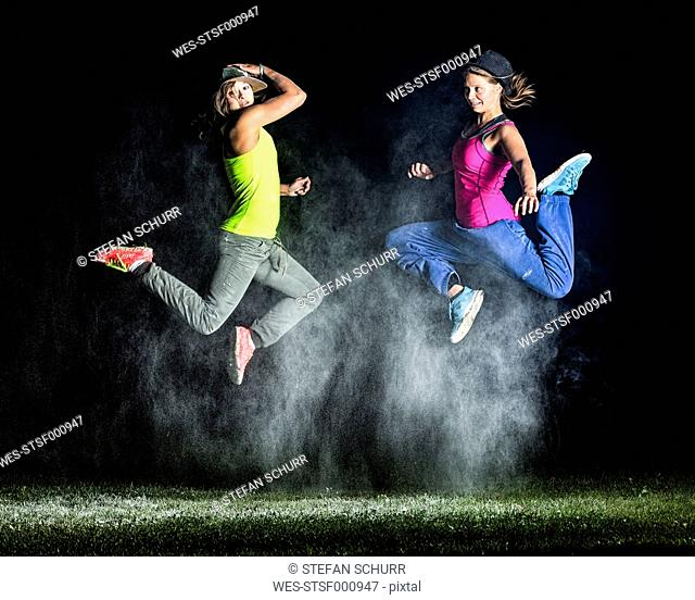 Two young women jumping in between cloud of flour in front of night sky