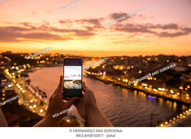 Woman's hands holding smartphone with a photo of panoramic view of Porto at sunset, Portugal