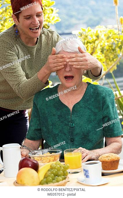 Elderly woman is surprised by daughter during breakfast