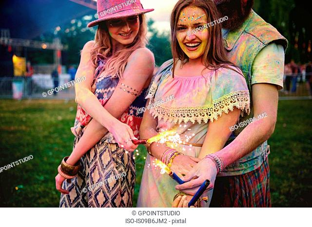 Portrait of two young women and covered in coloured chalk powder at festival