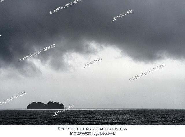 Canada, BC, Sunshine Coast. Dark rain clouds loom over offshore island in the Strait of Georgia, north of Vancouver