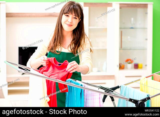 Young woman ironing clothing at home