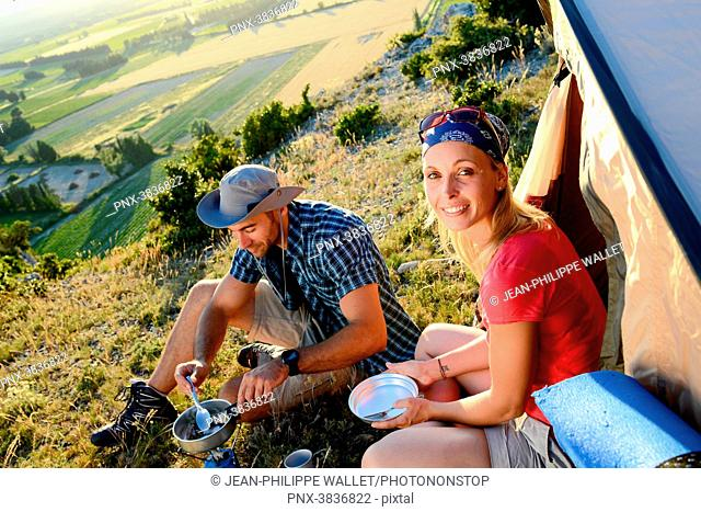 Young couple in a tent camp on summer outdoor adventure hiking trip