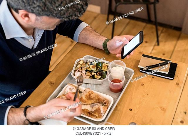 Businessman using smartphone and eating grilled chicken in restaurant