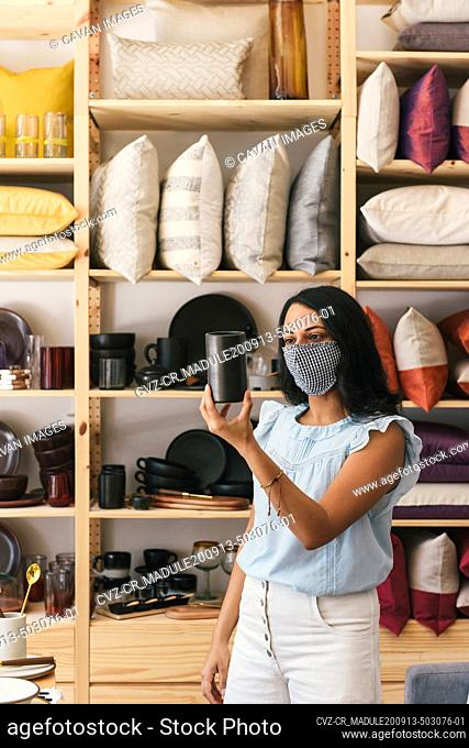 Woman with mask on looking at black ceramic cup in fancy home store