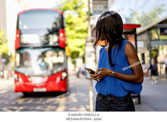 Female Afro-American using smartphone at bus stop in London, United Kingdom