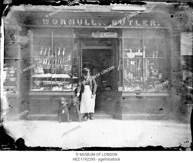 Exterior of Wormull & Cutler, a hardware shop, (late 19th century?). The shopkeeper, wearing a top hat, stands in the doorway with two dogs