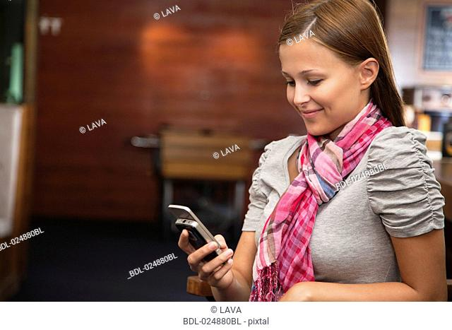 young woman looking at display of her mobile phone