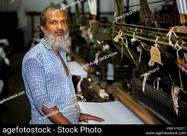 A yarn factory worker has made white cotton cloth in the machine at Narsingdi, Bangladesh