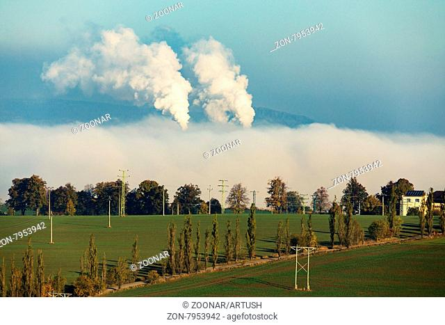 non ecologic smoking chimneys in from factory hidden in morning mist over rural landscape