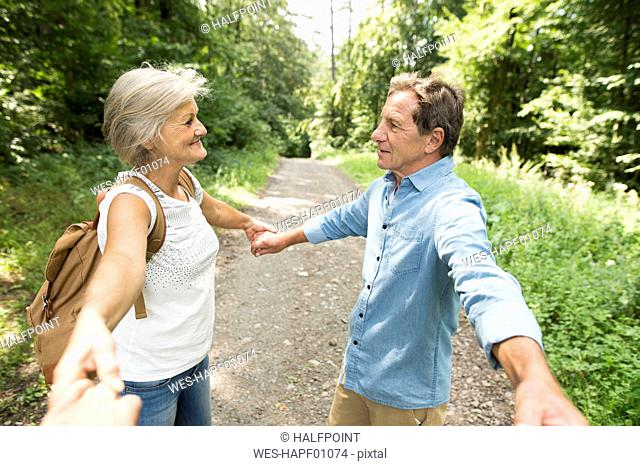 Senior couple holding hands with third person on forest track